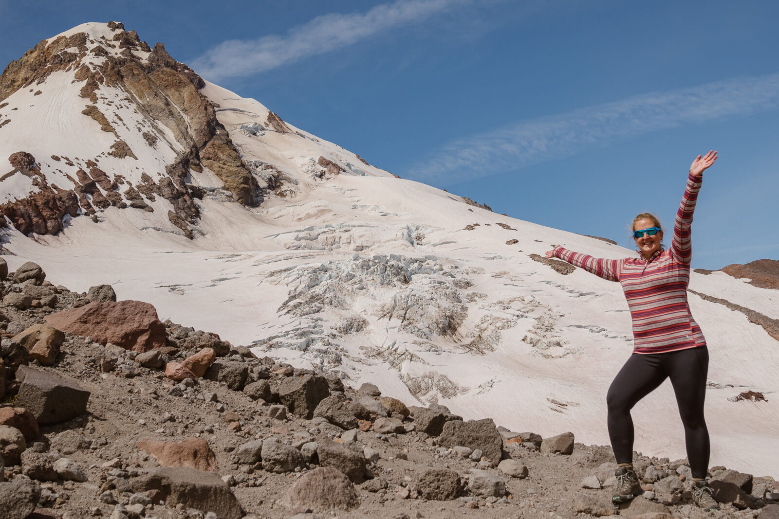 Photographer stands on trail near the top of Mount Hood on a sunny day